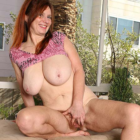 Mature busty redhead Breeze touches herself