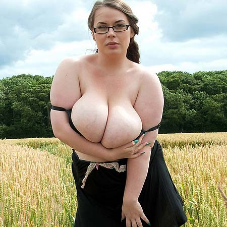 Busty Gina G. strips outside in a field