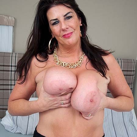 Busty and mature Lulu Lush strips on her bed