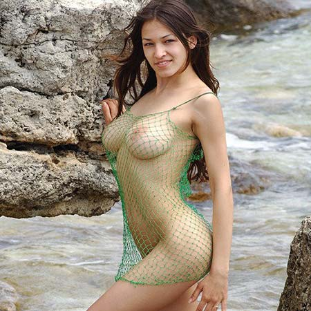 Big boobed Sofi in a fishnet outfit on the rocks